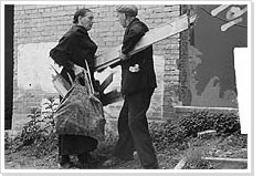 A man and woman quarrelling over a plank of wood clandestinely salvaged from an unoccupied building at the time of the fuel shortage caused in The Hague by the railway strike (1944-1945)